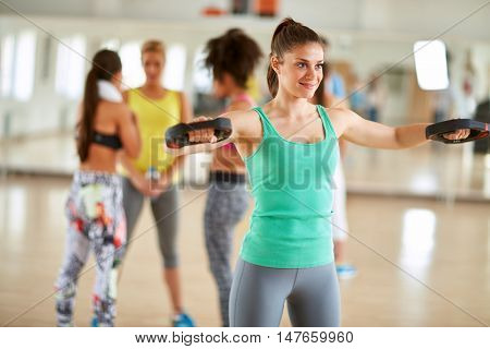 Young female exerciser use exercise equipment for arms in gym