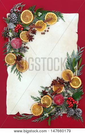Christmas border with dried fruit and spice, holly, mistletoe and snow covered cedar cypress on old parchment paper over red background.