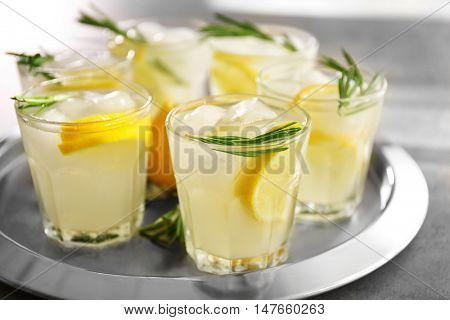 Cold fresh cocktail with lemon on metal tray