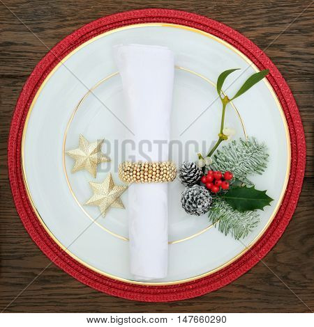 Christmas dinner decorative table setting with white porcelain plate, linen napkin and ring, holly, mistletoe, fir,  and gold star decorations on red mat over oak background.