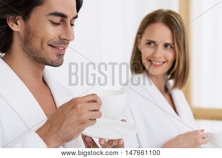 Relaxing and unwinding. Close up photo of handsome man in white bathrobe drinking tea in spa with smiling woman in background