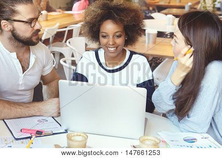 Three Students Of Different Ethnic Groups At Coffee Shop Chatting With Their Mates Online Using Lapt