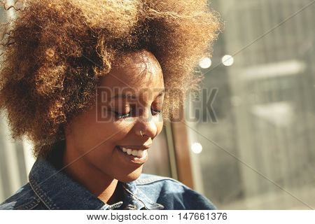 Outdoor Portrait Of Stylish Attractive Dark-skinned Student Girl With Afro Haircut And Facial Pierci