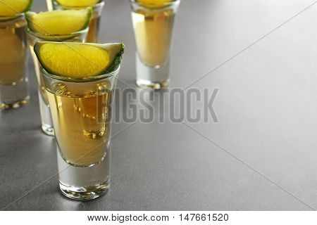 Shots of gold tequila with lime slices on light background