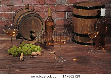 Glasses of white wine, grapes and wooden barrels on a brick wall background