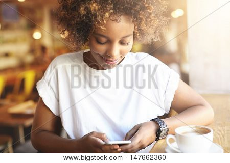 Portrait Of Fashionable African Brunette Female With Afro Haircut Using High-speed Internet Connecti
