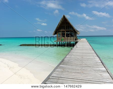 Maldives. A footpath goes to the bungalow, which is in the ocean.