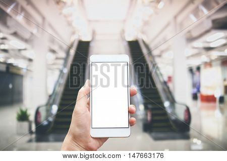 Business conceptual- Focused on left hand holding mobile on escalator at shopping mall blurred background