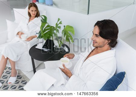Ready for spa treatment. Top view of handsome man drinking tea, relaxing in chair in spa center with woman in background