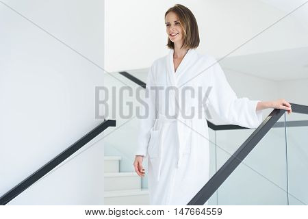 This is how I relax. Cropped shot of pretty brunette woman wearing white bathrobe and coming down stairs in hotel spa