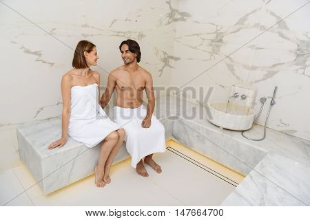This sauna feels amazing. Loving couple spending time in sauna while enjoying weekend in spa center