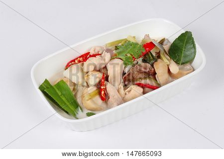 Chicken and galangal in coconut milk soup and herb on white background. Side view