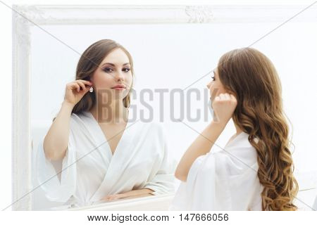 Young and beautiful girl trying earrings. Bride doing make-up near the mirror.