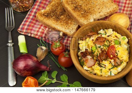 Scrambled eggs with fried bacon. English breakfast. Toast and scrambled eggs with chives. Recipe for a healthy meal.