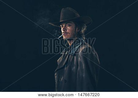 Retro Cowboy Smoking Cigarette. Young Man. Studio Shot.
