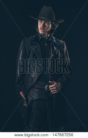 Confident Vintage 1900 Cowboy Showing Revolver. Ready To Shoot. Studio Shot.