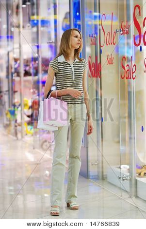 Girl in shopping mall looking on a show-window with