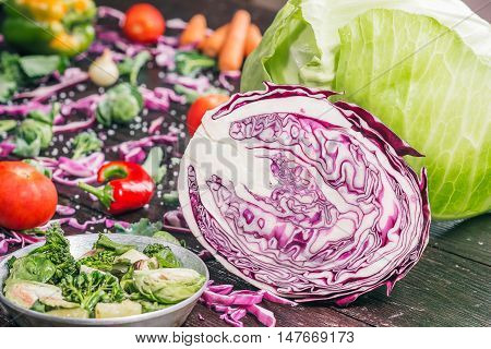 Green and red cabbage, broccoli, brussel sprouts, carrot, paprika, chili, tomatoes and other vegetable on the dark wooden surface