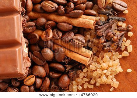 Coffee beans, cinnamon, sugar, chocolate & clove. Close up.