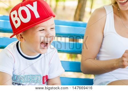 Mother and son playing together outdoors in park laughing fells fun and happy