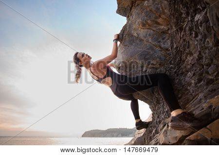Young female rock climber climbing challenging route on overhanging cliff . Summer time.