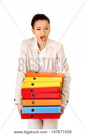 Businesswoman holding heavy bidners.