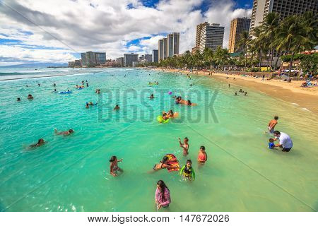 Waikiki Oahu HI - August 27 2016: children play in the crowded Kuhio Beach called The Ponds because a concrete wall makes calm water and safe. Kuhio Beach is great for boogie boarding.