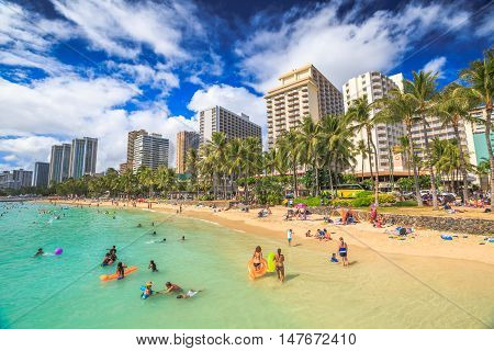 Waikiki Oahu HI - August 27 2016: summertime in crowded Prince Kuhio Beach also called The Ponds because a concrete wall makes the water calm and sicura. Kuhio Beach is a section of Waikiki Beach.