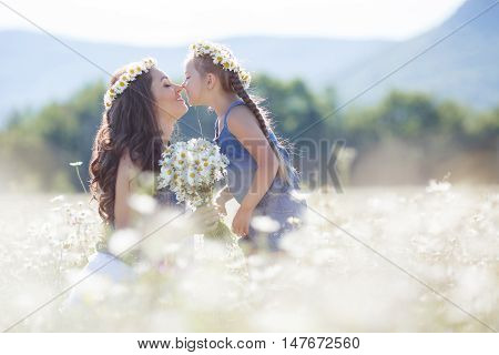 Cheerful family of two people,mother and little daughter spend time together in the highlands on a field of blooming white daisies in summer in the fresh air,mother and daughter wearing wreaths of flowers-white daisies,both brunettes,girl with pigtails