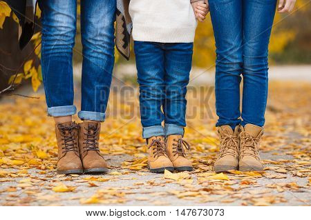 Happy young family,father,mother and little daughter in the autumn Park,all three dressed in blue jeans and brown shoes,standing next to each other on the yellow of autumn leaves the alley of the Park,hold each other's hands,pay attention to the feet