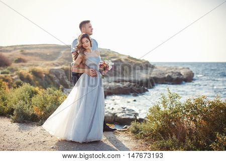 A young couple in love,bride and groom,in their wedding clothes, standing arm in arm on top of the cliffs against the blue of the ocean outside in the summer time,in the hands of the bride has a beautiful wedding flower bouquet with white Lily