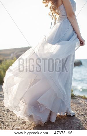 Young bride in long white wedding dress,off-shoulder beautiful long curly blonde hair,bride posing alone, standing on a rocky coast sex trafficking against the clear blue sky and ocean in summer time in fresh air