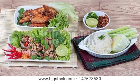 Sticky rice served with fried chicken and  spicy sour mixed herb salad of chicken and liver chicken on wood. Side view.