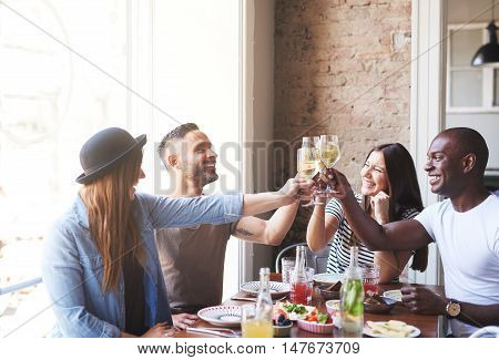 Two pair of diverse male and female young adult couples celebrating with drinks after eating together at table in restaurant