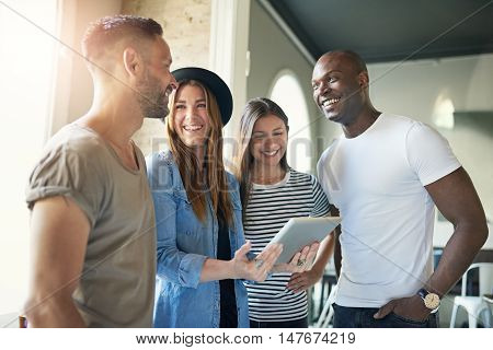 Successful young business team of enthusiastic modern young people in informal clothing standing in the office having a meeting grouped around an attractive young woman holding a tablet