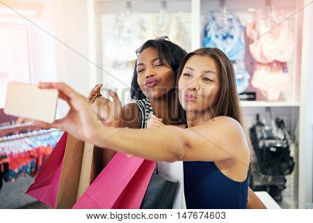 Playful young women flirting with the camera on their mobile phone as they pose for a selfie in a clothing store pouting their lips for a kiss