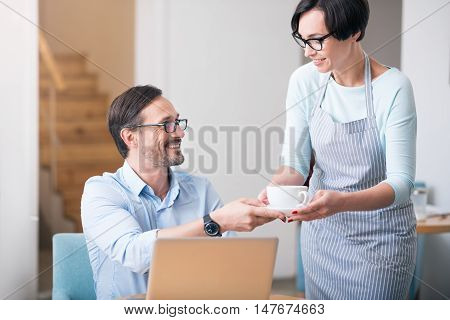 Best client. Cheerful waitress giving cup of coffee her positive client using laptop