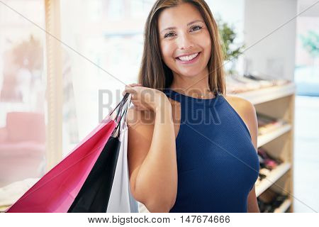 Smiling proud young female shopper grinning with pleasure as she stands in a fashion boutique with her shopping bags over her shoulder
