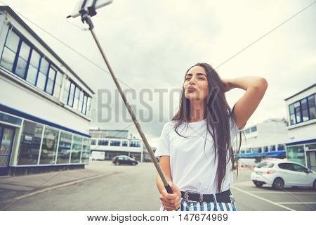 Wide angle view of beautiful young woman taking her own picture while kissing the air in the middle of street under cloudy sky with copy space