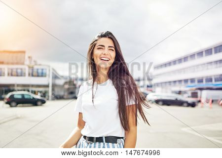 Happy woman giggling while standing outside in large parking lot with cars in background. Includes copy space.