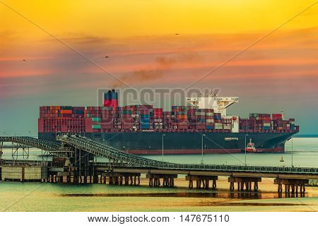 Tugboat assisting container ship on sea in the morning.