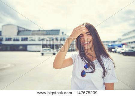 Cute woman with sunglasses on shirt fixes her hair as it blows in the wind at large parking lot