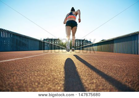 Lean athletic female runner caught mid flight as she sprints towards the sun hiding behind apartment buildings