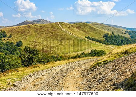 winding road through large meadows on the hillside of mountain range