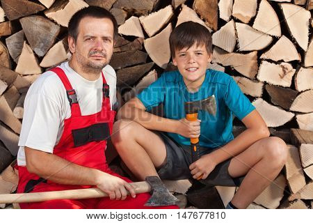 Man and boy sitting together in front of chopped wood stacked in the shed