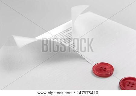 document under a blank sheet of paper with curled edges and buttons