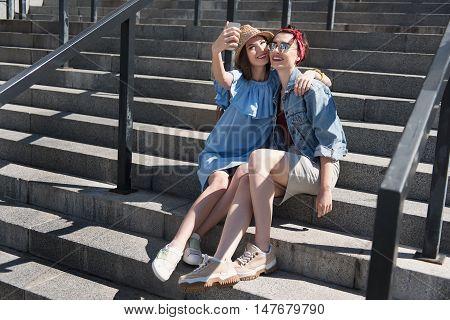 selfie time, two young beautiful girls taking a selfie
