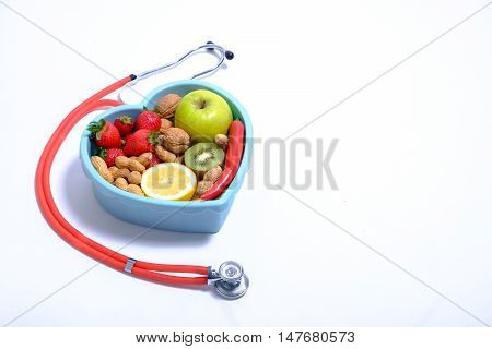 Heart shaped dish with vegetables and stethoscope isolated on white background