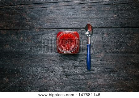 Can of raspberry marmalade on the dark wood surface. Flat lay