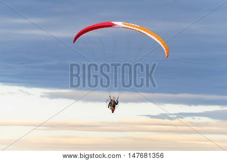 Paraglider flying in the sea of dark clouds